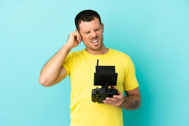Homme brésilien tenant une télécommande de drone sur fond bleu isolé frustré et couvrant les oreilles