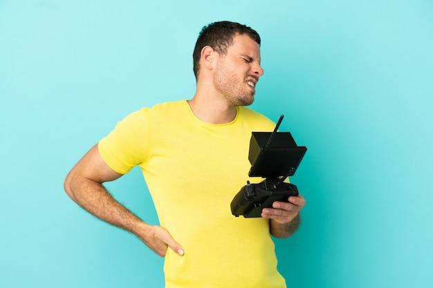Homme brésilien tenant une télécommande de drone sur fond bleu isolé souffrant de maux de dos pour avoir fait un effort