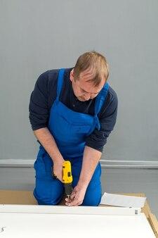 Un homme, un bricoleur en combinaison bleue, assemble une table en gros plan