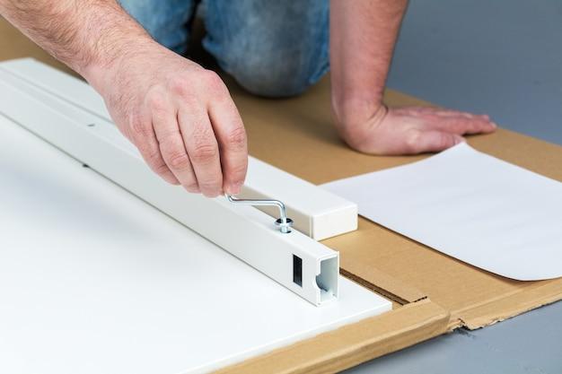 Un homme, un bricoleur dans une chemise bleue, recueille une table, gros plan
