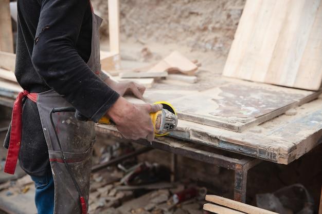 Un homme broie du bois à l'aide d'une ponceuse charpentier travaille avec un bois