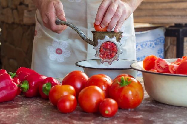 Un homme broie des tomates et des poivrons dans un hachoir à viande pour préparer la sauce lecho
