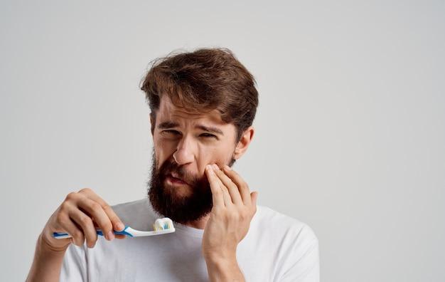 Homme avec une brosse à dents dans sa main soins de la cavité buccale matin procédures