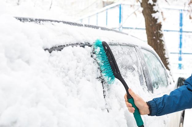 Un homme brosse la neige d'une voiture après une chute de neige.