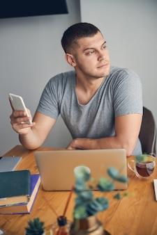 Homme brun concentré aux yeux bleus travaillant en ligne à domicile tout en tenant un mobile dans les mains et en contemplant