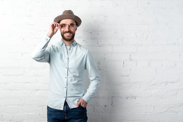 Homme brune à barbe portant en chemise, chapeau et lunettes joyeux souriant et touchant les lunettes. copyspace