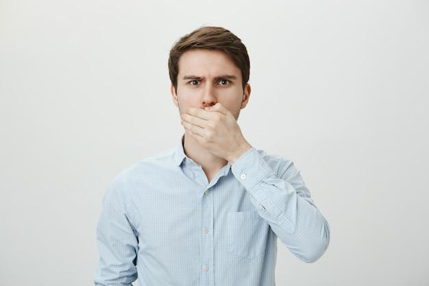 Homme brune bouleversé choqué ferme la bouche avec la main