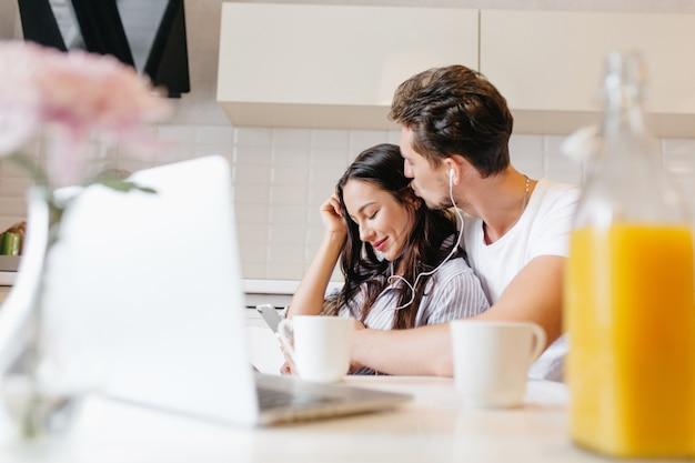 Homme brune avec une coupe de cheveux élégante embrassant les cheveux de sa femme, écoutant de la musique avec elle