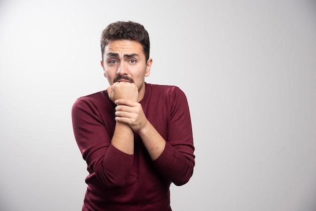 Un homme brune effrayé sur un mur gris.