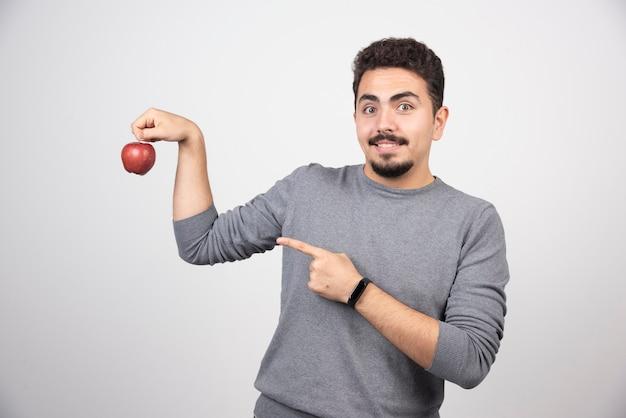 Homme brune pointant sur la pomme rouge sur fond gris.