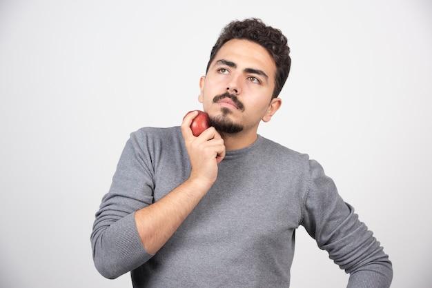 Homme brune avec pomme rouge pensant à quelque chose.