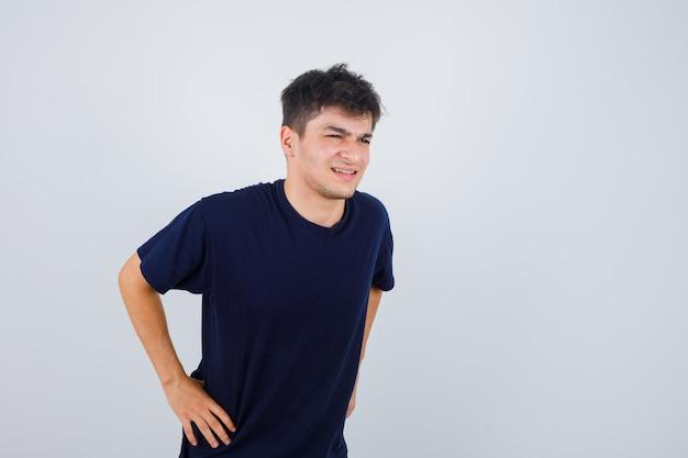Homme brune posant avec les mains sur la taille en t-shirt et à la joyeuse. vue de face.