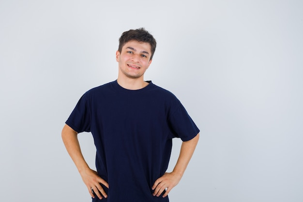 Homme brune posant avec les mains sur la taille en t-shirt et regardant joyeux, vue de face.