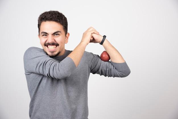 Homme brune posant avec pomme rouge sur fond gris.