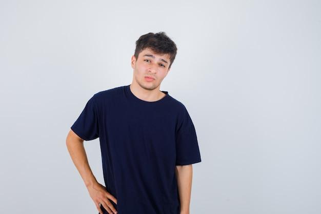 Homme brune posant en regardant la caméra en t-shirt et à la recherche de confiance. vue de face.
