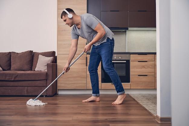 Homme brune séduisant avec un bâton de vadrouille pour laver le sol tout en écoutant de la musique dans les écouteurs
