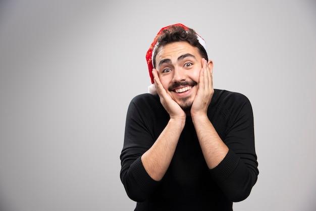 Un homme brune souriante au chapeau du père noël debout et posant