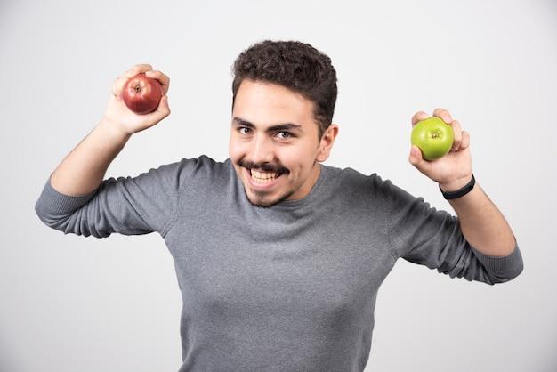 Homme brune tenant joyeusement des pommes vertes et rouges.
