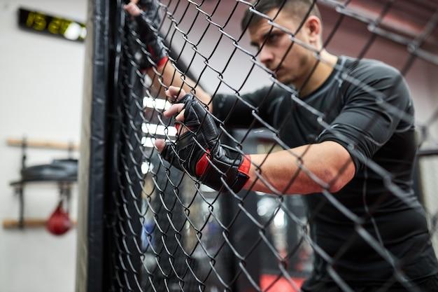 Un homme brune en vêtements noirs et gants pratique le kickboxing, le concept de sport mma, se tient épuisé et fatigué après s'être battu. portrait vue de côté. reposez-vous, regardez à travers la cage. se concentrer sur les mains dans les gants