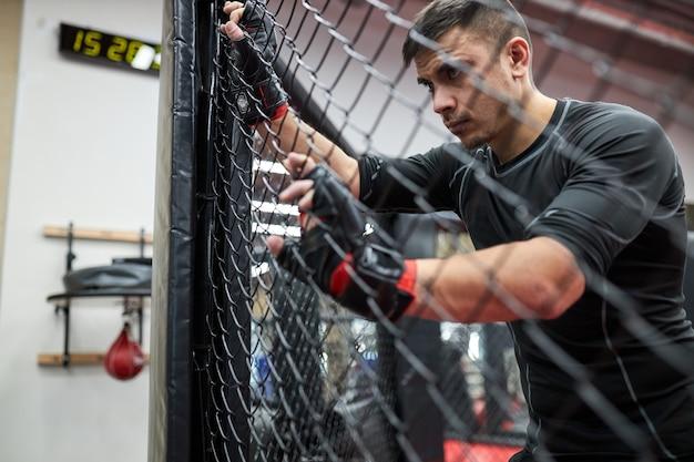 Un homme brune en vêtements noirs et gants pratique le kickboxing, le concept de sport mma, se tient épuisé et fatigué après s'être battu. portrait vue de côté. reposez-vous, regardez à travers la cage