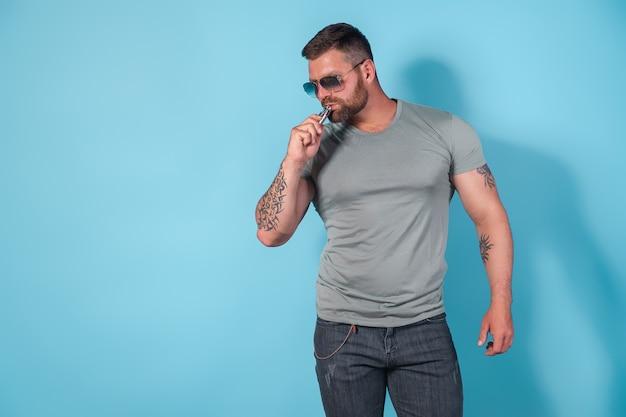 Homme brutal barbu dans des lunettes de soleil fumant une cigarette à vapeur comme alternative au tabac sur bleu