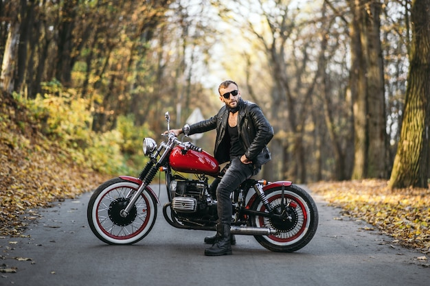 Homme brutal barbu en lunettes de soleil et veste en cuir assis sur une moto sur la route dans la forêt
