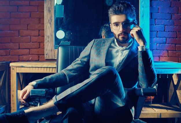 Homme brutal en costume élégant et lunettes dans le salon de coiffure