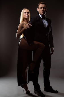 Un homme brutal en costume et une femme magnifique en robe de soirée noire avec un décolleté profond posent contre une surface de studio sombre