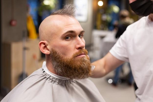 Homme brutal européen avec une barbe coupée dans un salon de coiffure