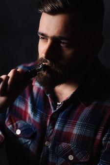 Homme brutal fumant une cigarette électronique