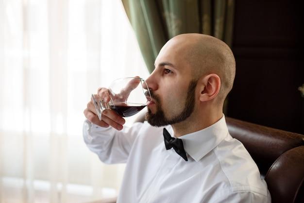Un homme brutal qui goûte au cognac.