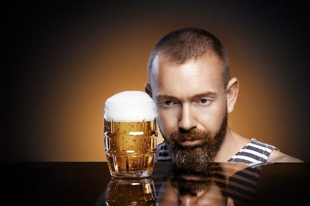 Homme brutal avec un verre de bière