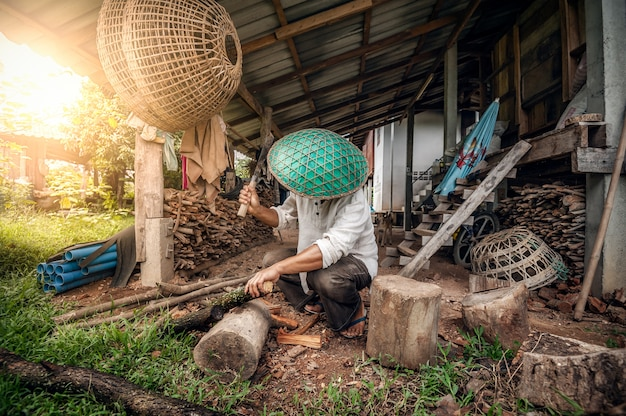 Un homme bûcheron coiffé d'un chapeau vert coupe un bois de chauffage avec une hache derrière sa maison.