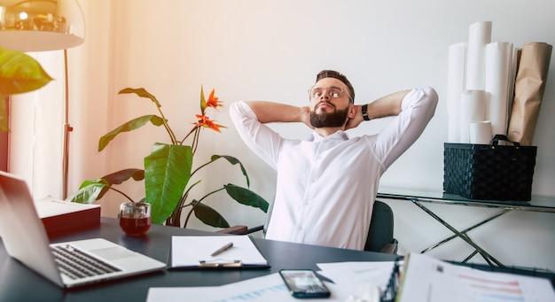 Un homme de bureau de barbe moderne qui réussit se repose après un travail acharné et bon dans son bureau