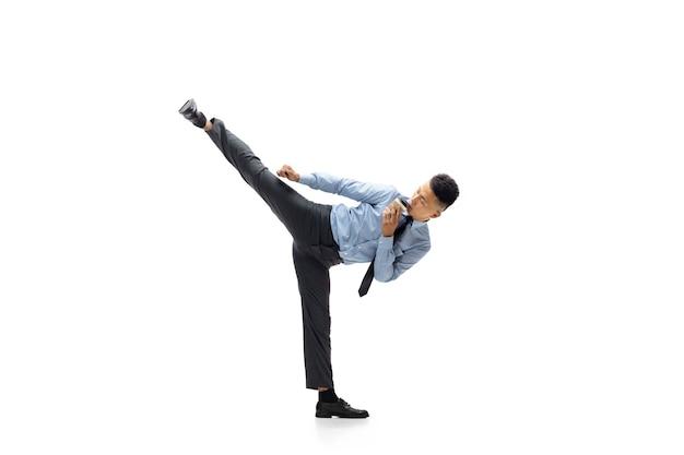 Homme de bureau pratiquant le taekwondo sur mur blanc