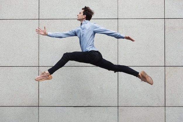 Homme de bureau sautant dans la ville, danseur de ballet