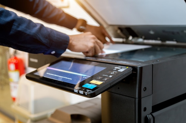 Homme bussiness appuyez sur le bouton de la main sur le panneau de l'imprimante, imprimante scanner laser bureau copie machine fournit début concept.