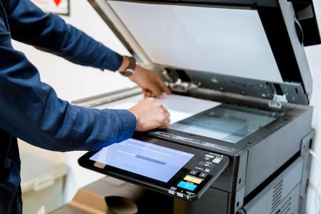 Homme bussiness appuyez sur le bouton de la main sur le panneau de l'imprimante