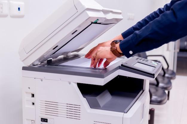 Homme de bussiness main appuyez sur le bouton sur le panneau de l'imprimante, imprimante scanner laser bureau copie machine fournit le concept de départ.
