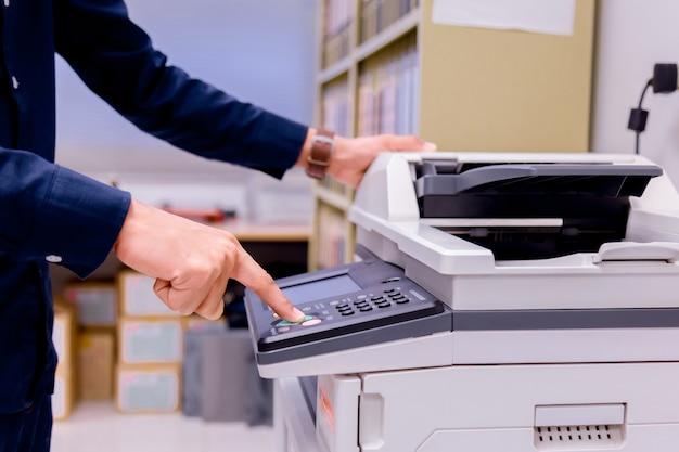 Homme bussiness main appuyez sur le bouton sur le panneau de l'imprimante.