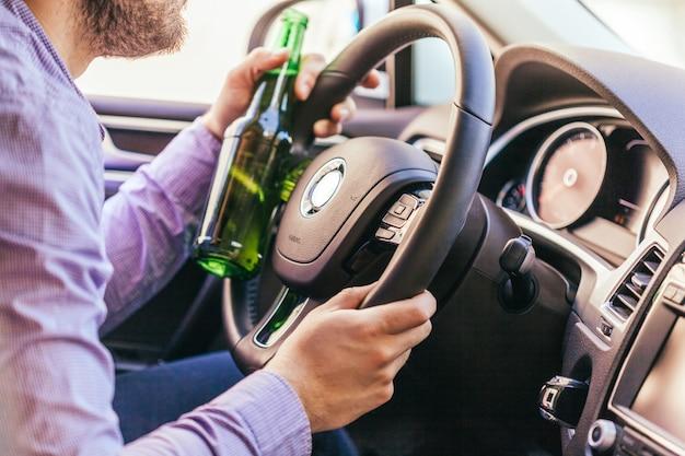 Homme buvant de l'alcool en conduisant la voiture