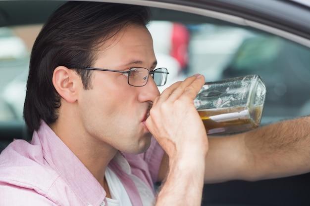 Homme buvant de l'alcool en conduisant