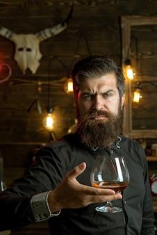 Homme buvant. bar rétro. bel homme pensif tient un verre de whisky ou de cognac