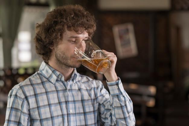 Homme buvant de la bière au bar