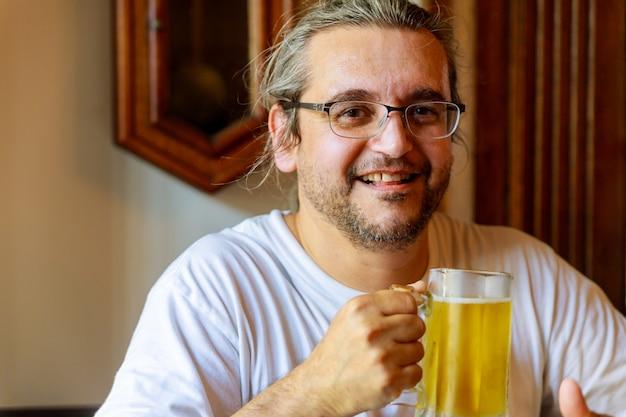 Homme buvant de la bière de bel homme buvant de la bière en position assise
