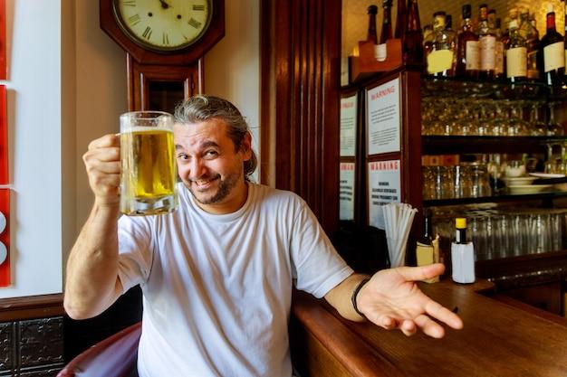 Homme buvant de la bière de bel homme buvant de la bière tout en restant assis au comptoir du bar