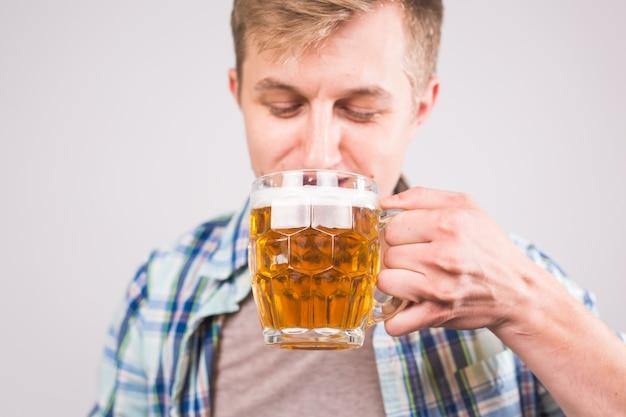 Homme buvant de la bière. heureux jeune homme tenant une chope de bière.