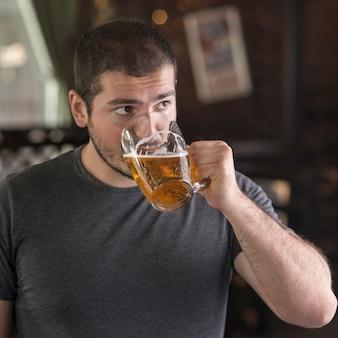 Homme buvant de la bière et regardant ailleurs