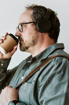 Homme buvant un café chaud tout en écoutant de la musique