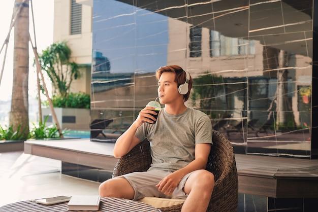 Homme buvant du café au bord de la piscine